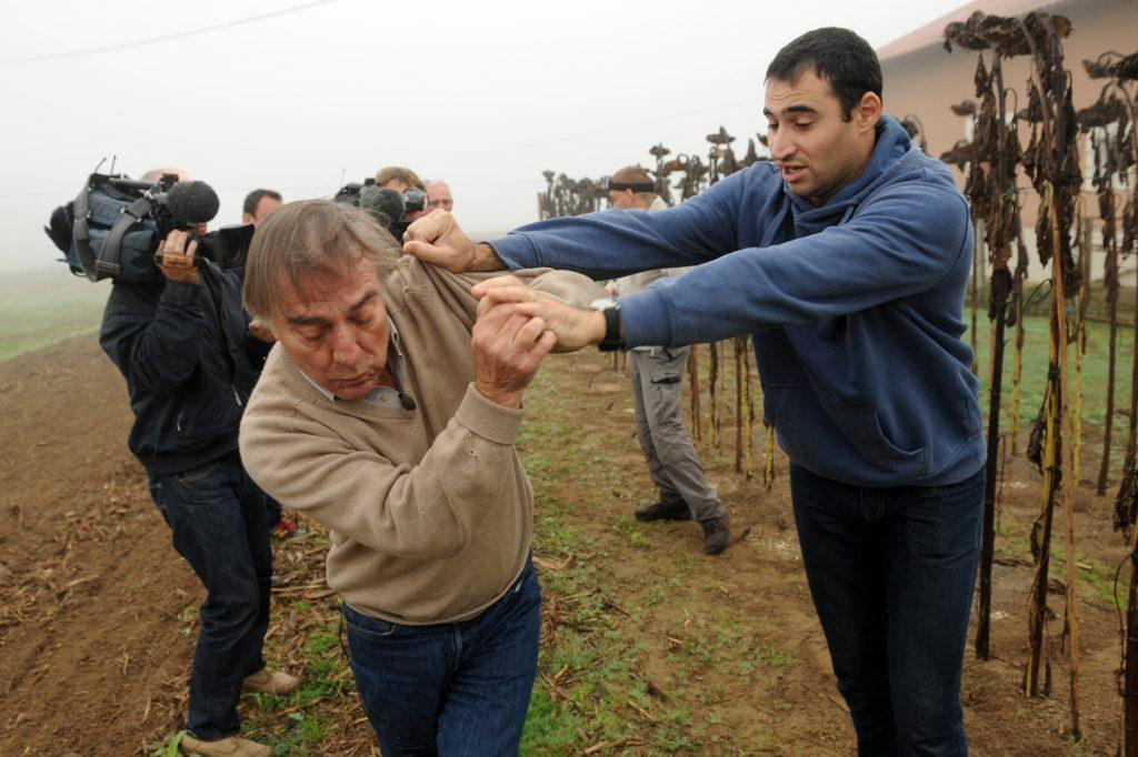 President of the Bird Protection league (LPO) Allain Bougrain-Dubourg (L) is evacuated by an inhabitant after clashing with the owner (unseen) of a plot where bird traps were found during an action against finch poaching, on November 9, 2015 in Audon, south western France. AFP PHOTO / GAIZKA IROZ